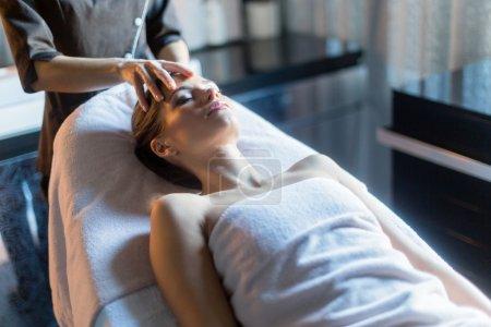 Photo pour Masseur de traiter le visage d'une femme belle, jeune, posé sur la table de massage - image libre de droit