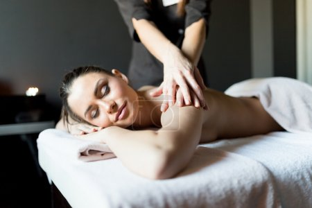 Lady having her body massaged by a masseur