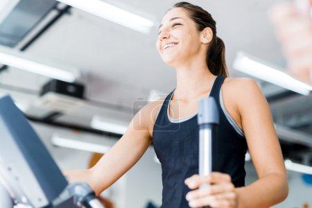 Photo pour Belle jeune femme utilisant l'entraîneur elliptique dans une salle de gym dans une humeur positive - image libre de droit