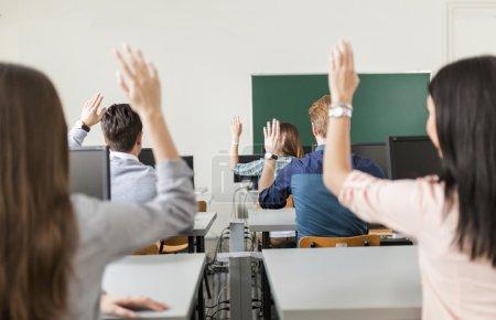 Photo pour De jeunes élèves levant la main dans une salle de classe montrant qu'ils sont prêts - image libre de droit