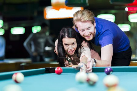 Man and woman flirting while playing billiard