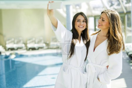 Ladies taking a selfie next to a swimming pool