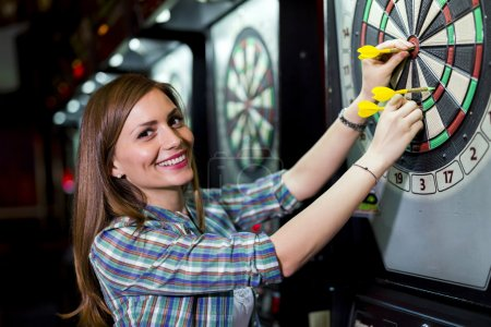 Woman playing darts in a club