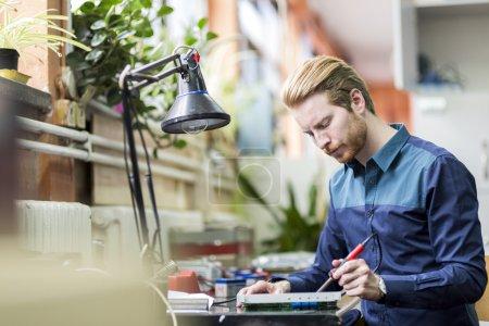 Photo pour Beau jeune homme un circuit imprimé de brasage et travaillant sur le matériel de fixation - image libre de droit