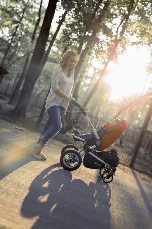 Mother walking child in a pram