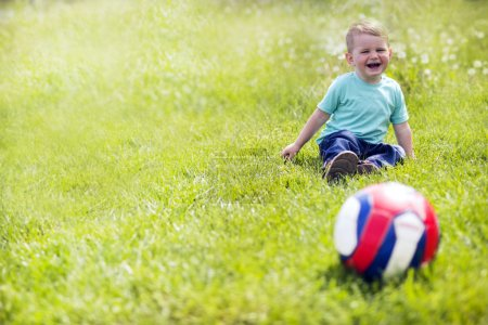 Photo for Adorable small boy playing with a soccer ball outdoors - Royalty Free Image