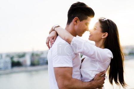 Photo pour Jeune couple romantique étreignant et sur le point de s'embrasser dans un beau coucher de soleil - image libre de droit