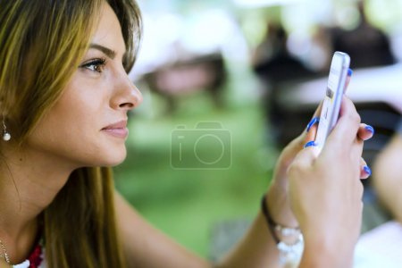 Beautiful woman texting somebody with her phone