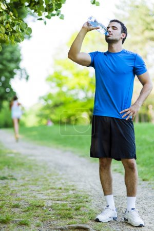 Photo for Young male athlete drinking water in the park after jogging - Royalty Free Image