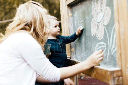 Mother and son drawing on blackboard with chalk