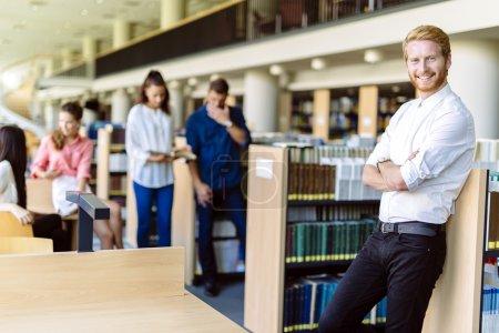 Photo pour Groupe de jeunes intelligents qui s'éduquent dans une bibliothèque - image libre de droit