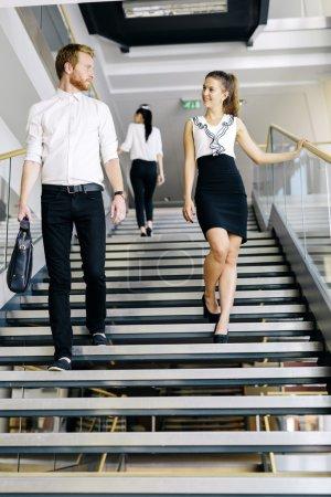 Photo pour Groupe d'hommes d'affaires marchant et prenant des escaliers dans un immeuble de bureaux - image libre de droit