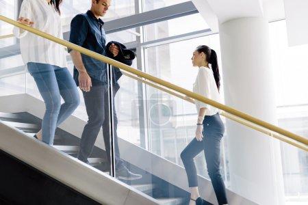 Photo pour Groupe de gens d'affaires marchant et prenant des escaliers dans un immeuble de bureaux - image libre de droit