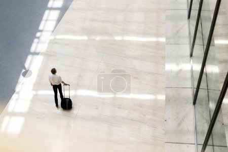 Photo for Handsome business holding a trolley and walking in a modern building seen from above - Royalty Free Image