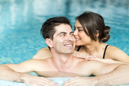 Couple relaxing by the side of the pool