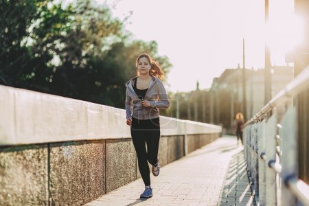 Fit woman jogging in city