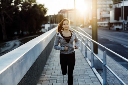 Photo for Beautiful female jogging in city and keeping her body in shape - Royalty Free Image