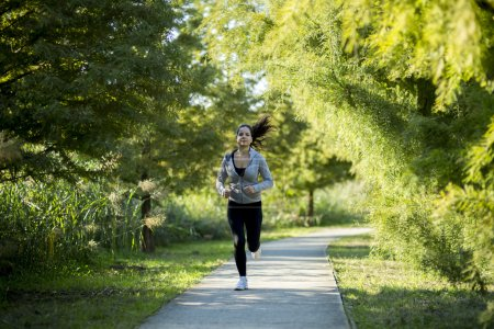 Photo for Woman running in park to keep herself in shape - Royalty Free Image