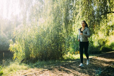 Photo for Fit female jogger running in nature surrounded by beautiful hanging trees - Royalty Free Image