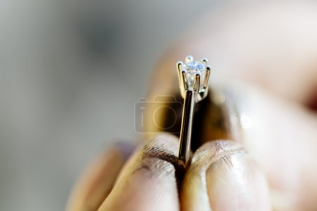 Ring held by jeweler after polishing