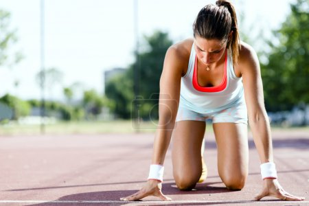Photo for Beautiful female sprinter getting ready for the run during summer - Royalty Free Image