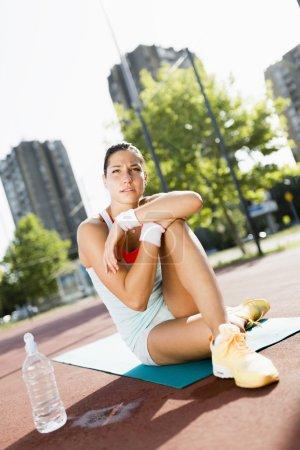 Sportswoman in the city taking a break