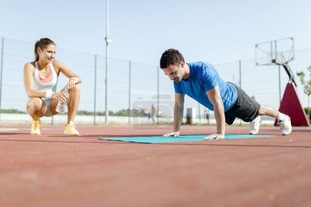 Personal trainer counting push-ups and motivating