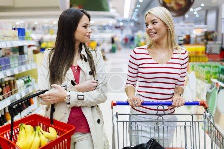 Photo pour Deux belles femmes faisant du shopping au supermarché - image libre de droit