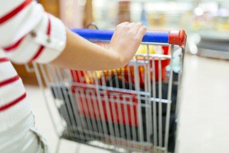 Photo pour Femme faisant du shopping dans un supermarché et remplissant son panier - image libre de droit