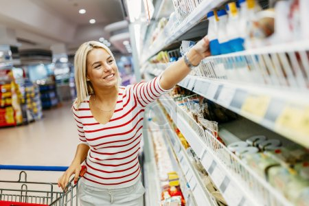 Photo for Beautiful woman shopping in supermarket and deciding what to buy - Royalty Free Image