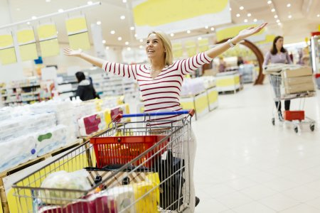 Photo for Woman happy when shopping in supermarket - Royalty Free Image