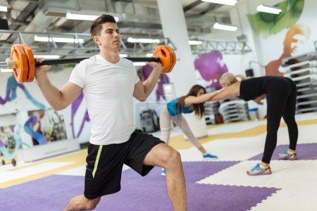 Photo pour Les gens formation lifiting des poids et centre de fitness - image libre de droit