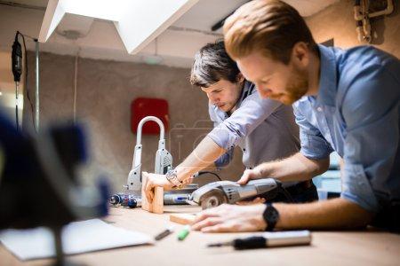 Photo pour Deux concepteurs travaillant dans l'atelier et la création de meubles sur mesure - image libre de droit