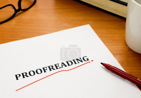 Proofreading word on white sheet with red pen, boo...