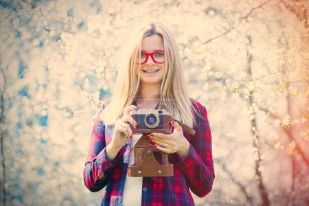 Photo pour Portrait de la belle jeune femme avec caméra près de la cerise en fleurs - image libre de droit