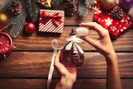 Photo pour Photo de la femelle les mains tenant des parfums, brosses sur le fond de décorations de Noël - image libre de droit
