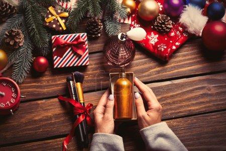 Photo pour Photo des mains féminines d'emballage parfum, brosses, radio-réveil sur le fond de décorations de Noël - image libre de droit