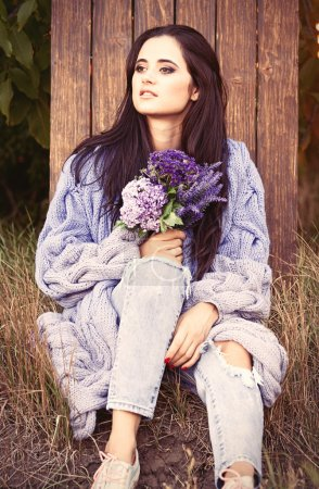 Photo pour Portrait d'une jeune fille brune aux fleurs à la campagne - image libre de droit