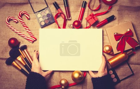Photo for Female hands are wrapping cosmetics in christmas gifts on jute background - Royalty Free Image
