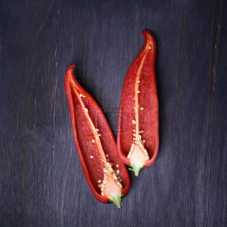 Fresh spicy red chilli pepper, sliced, on wooden background.