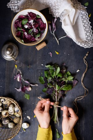 Herbs, gathered into a bunch and tied, over rustic table with salad and farm eggs. Overhead view. Healthy diet background.
