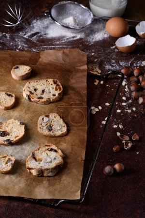 Baked bread rusks with raisins and nuts, cooking ingredients over rustic kitchen table. Hazelnut biscuits, crispy appetizers.