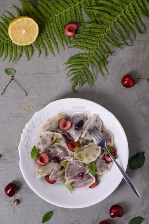 Photo for Cherry dumplings, made with wonton wrappers and cherries. Traditional russian cuisine recipe, Top view. - Royalty Free Image