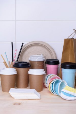 Coffee and tea cups for on the go. Paper and thermo mugs for hot or cold drinks on wooden bar counter. White background.