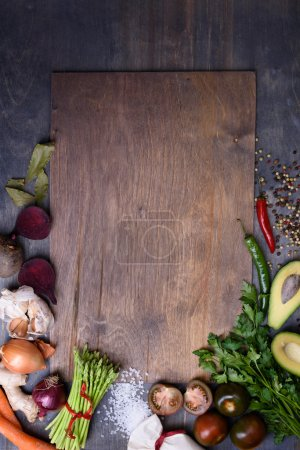 Healthy food background on wooden board. Vegetable menu. Top view, copy space.