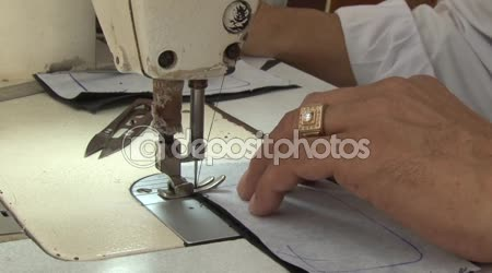 Textile Garment Factory Workers: ECU male hands and sewing machine needle