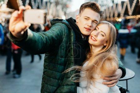 Happy couple taking selfie on the street