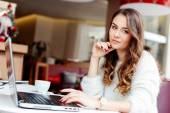 Dívka sedí v kavárně s notebookem