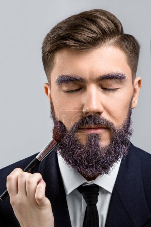 Photo for Brunette man with violet beard, wearing in dark blue suit and tie. Woman's hand with make-up brush near his face, on white background, in studio, close up - Royalty Free Image