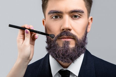 Photo for Brunette man with violet beard and eyebrows, wearing in dark blue suit and tie, looking at camera. Woman's hand with make-up brush near his face, on white background, in studio, close up - Royalty Free Image